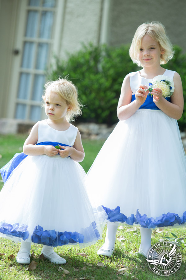 Fun wedding photographer at Kindred Oaks in Austin, Texas - flower girls in white and royal blue dresses