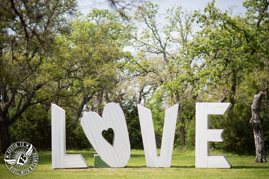 Fun wedding photographer at Kindred Oaks in Austin, Texas - LOVE sign in the meadow