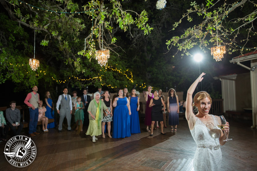 Fun wedding photographer at Kindred Oaks in Austin, Texas - bride throws bouquet to single ladies with Dexter Kyner, DJ for Hire