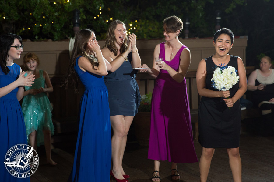 Fun wedding photographer at Kindred Oaks in Austin, Texas - single ladies catch bouquet with Dexter Kyner, DJ for Hire