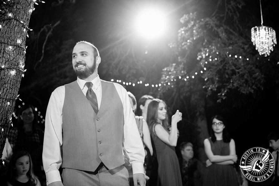 Fun wedding photographer at Kindred Oaks in Austin, Texas - groom about to throw the garter with Dexter Kyner, DJ for Hire