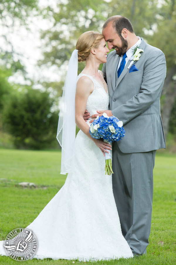Fun wedding photographer at Kindred Oaks in Austin, Texas - bride and groom in the meadow with blue hydrangea and white calla lily bouquet