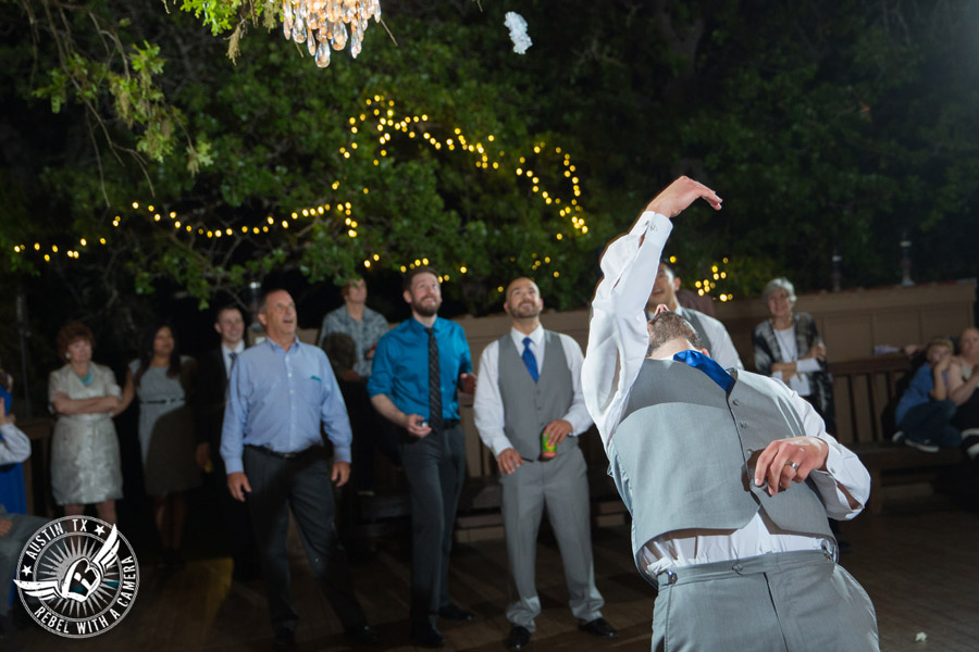 Fun wedding photographer at Kindred Oaks in Austin, Texas - groom throws the garter with Dexter Kyner, DJ for Hire