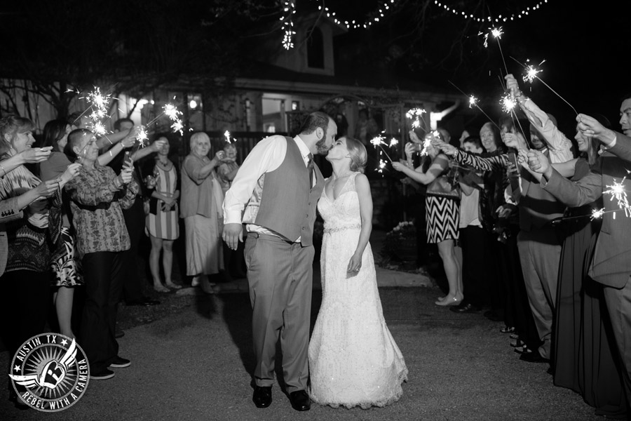 Fun wedding photographer at Kindred Oaks in Austin, Texas - bride and groom kiss as they walk out to sparkler exit
