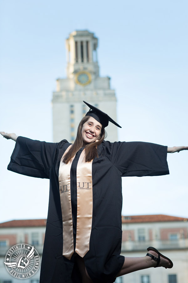 Longhorn graduation pictures on the UT Austin campus - graduate in cap and gown in front of the UT tower