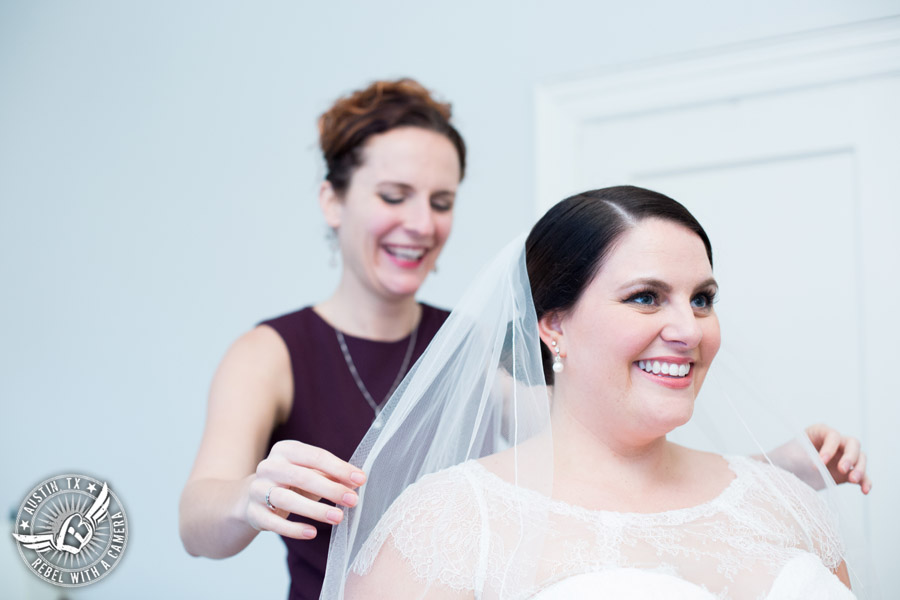 Fun wedding pictures at the Texas Federation of Women's Clubs Mansion - bridesmaid helps smiling bride get ready - Vain Salon - Nicole Schultz Make-Up - Belle Saison Bridal Salon