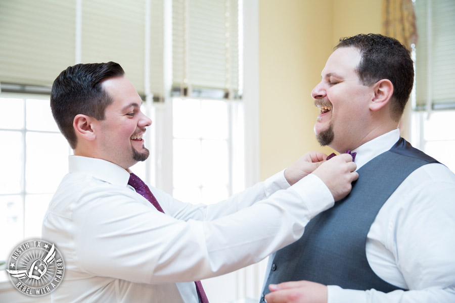 Fun wedding pictures at the Texas Federation of Women's Clubs Mansion - groomsman adjusts groom's purple bow tie