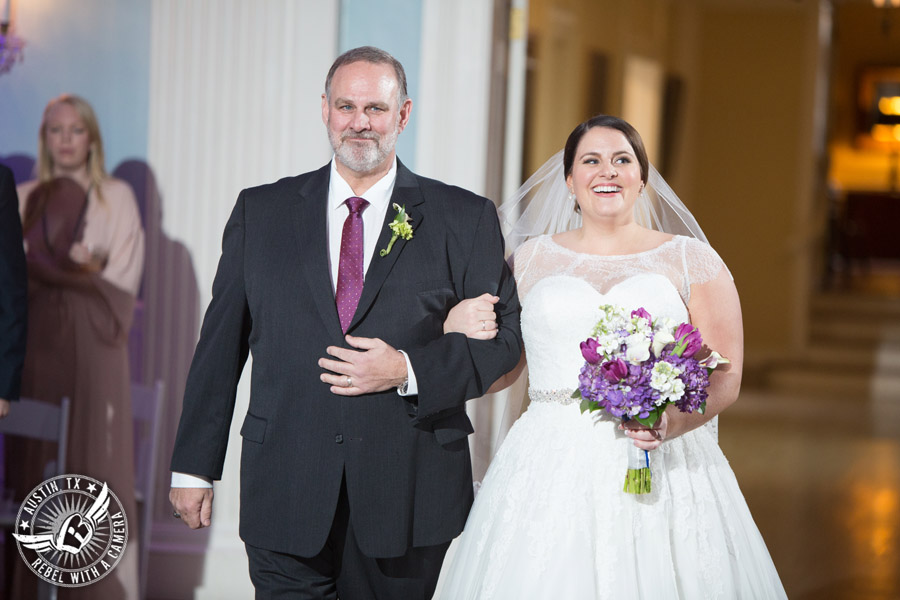 Fun wedding pictures at the Texas Federation of Women's Clubs Mansion - bride is escorted down the aisle by her father during the wedding ceremony - Freytag's Florist - purple hydrangea and purple tulip bouquet