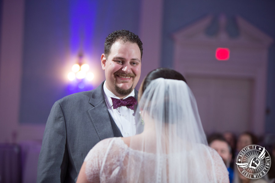 Fun wedding pictures at the Texas Federation of Women's Clubs Mansion - groom looks lovingly at bride during the wedding ceremony