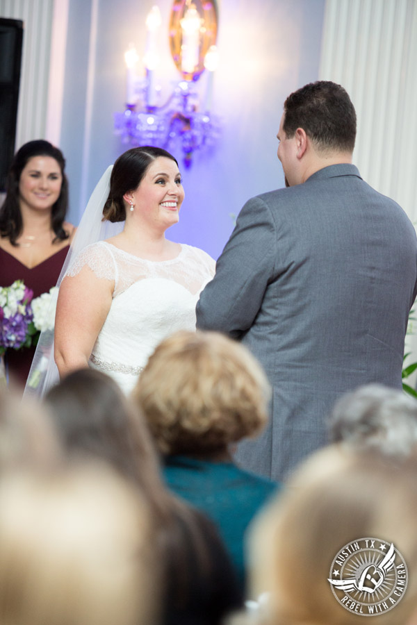 Fun wedding pictures at the Texas Federation of Women's Clubs Mansion - bride looks lovingly at groom during the wedding ceremony