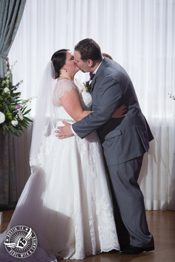 Fun wedding pictures at the Texas Federation of Women's Clubs Mansion - bride and groom kiss during the wedding ceremony