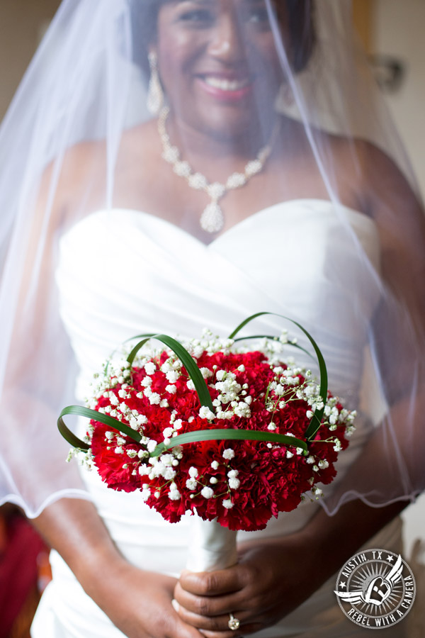 Picture of bride with red carnation bouquet from HEB Blooms in the bride's room at Chapel Dulcinea in Driftwood, TX - Austin Wedding Planners by Rosa