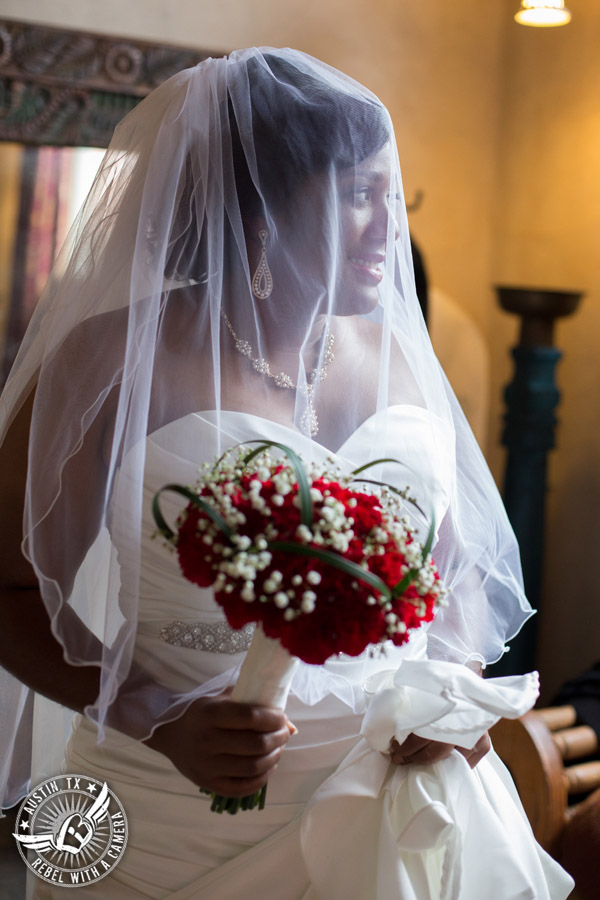 Picture of bride with red carnation bouquet from HEB Blooms in the bride's room at Chapel Dulcinea in Driftwood, TX