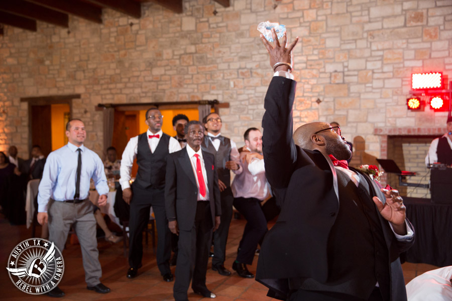 Pictures of weddings at Thurman's Mansion in Driftwood, TX - groom throws the garter from the bride during the wedding reception - Austin Wedding Planners by Rosa