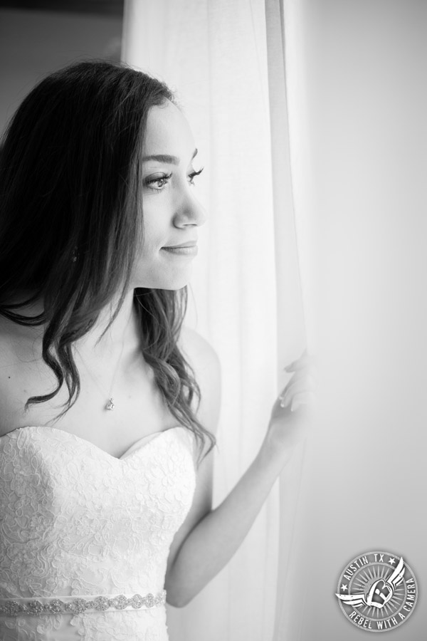 Lone Oak Barn wedding photos - bride looks out the window in the bridal suite