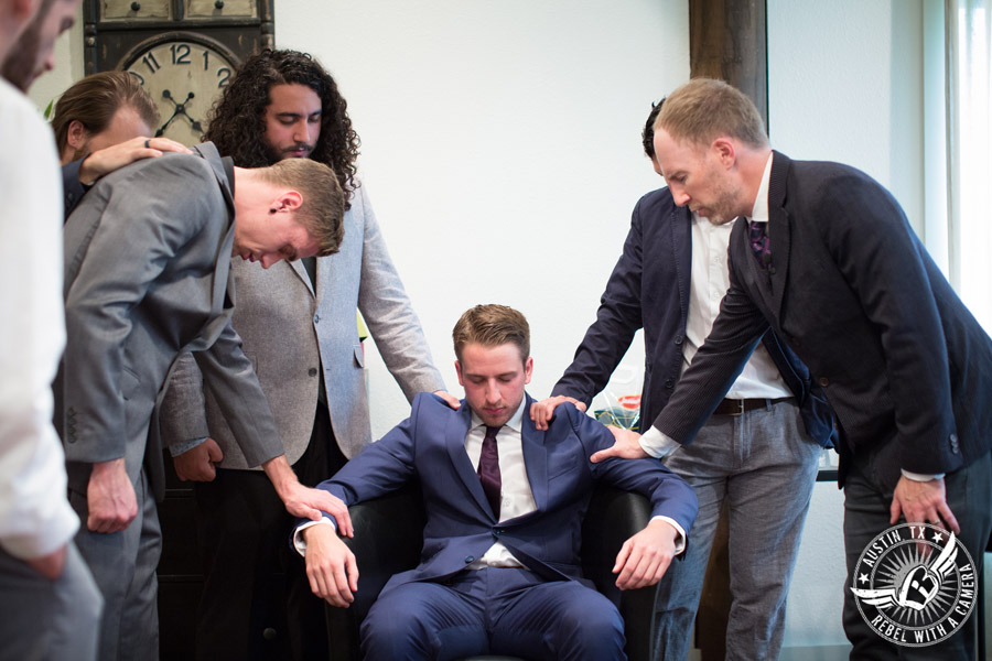 Lone Oak Barn wedding photos - groom and groomsmen pray with the minister in the groom's room