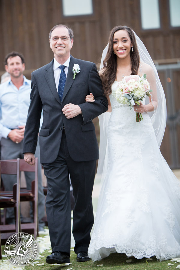Lone Oak Barn wedding photos - bride sees groom as she walks down the aisle with her father during the wedding ceremony