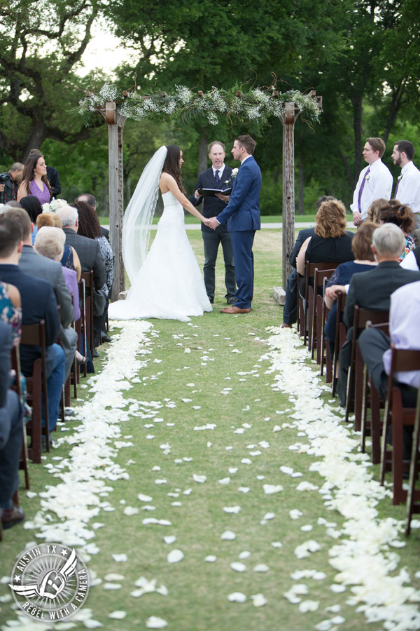 Lone Oak Barn wedding photos - bride looks lovingly at the groom during the wedding ceremony with rose petals lining the aisle