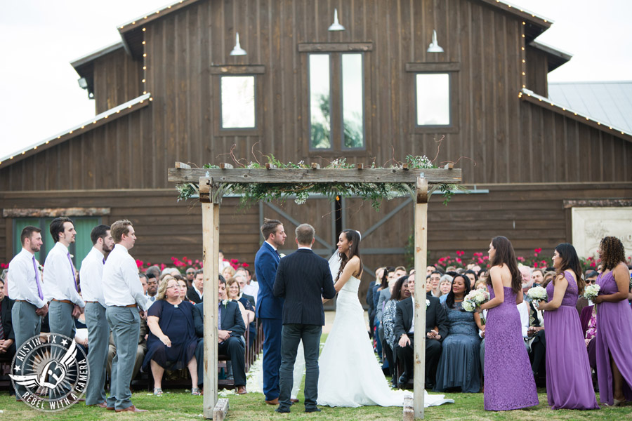 Lone Oak Barn wedding photos - bride looks lovingly at the groom during the wedding ceremony in front of the barn
