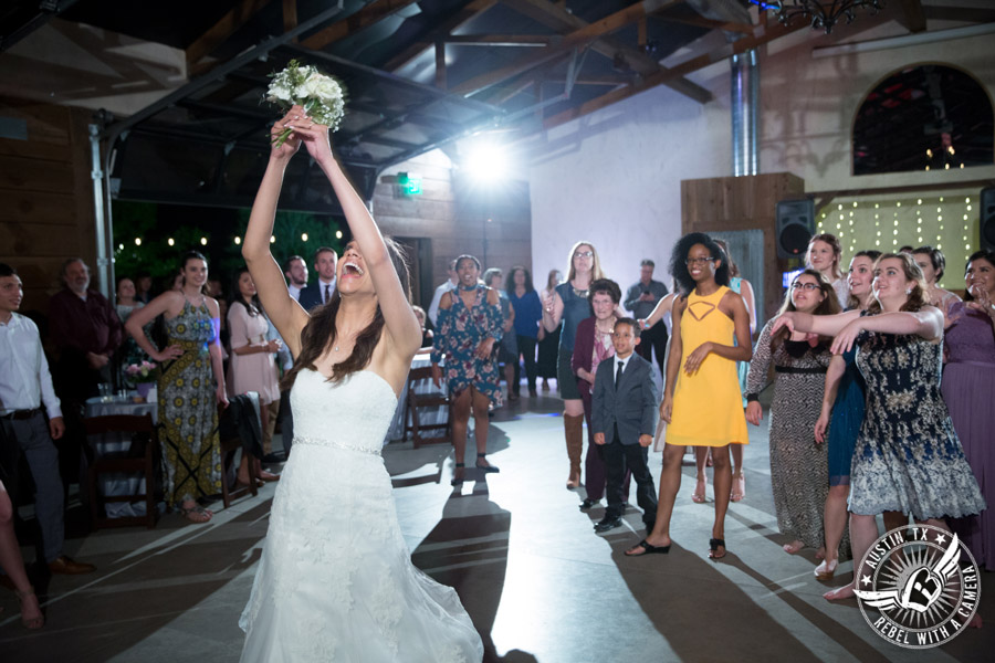 Lone Oak Barn wedding photos - bride tosses bouquet to all the single ladies at the wedding reception in the South Hall