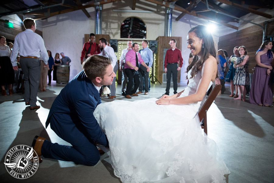 Lone Oak Barn wedding photos - groom takes the garter off the bride at the wedding reception in the South Hall