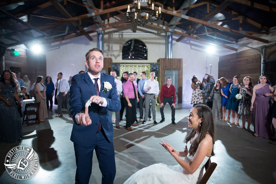 Lone Oak Barn wedding photos - groom tosses the garter to the single guys at the wedding reception in the South Hall