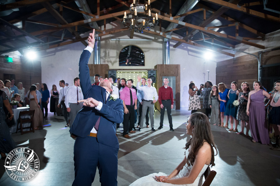 Lone Oak Barn wedding photos - groom tosses the garter to the single guys at the wedding reception
